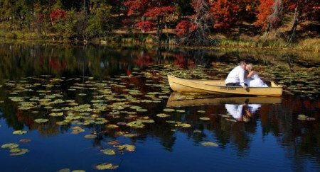 Bride and groom sitting in a boat on the lake after their weddings